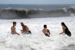People play in the high surf from the Atlantic Ocean on the barrier island in Vero Beach, Fla., Sunday, Sept. 1, 2019. The barrier island is under a voluntary evacuation today and a mandatory evacuation tomorrow in preparation for the possibility of Hurricane Dorian making landfall. (AP Photo/Gerald Herbert)