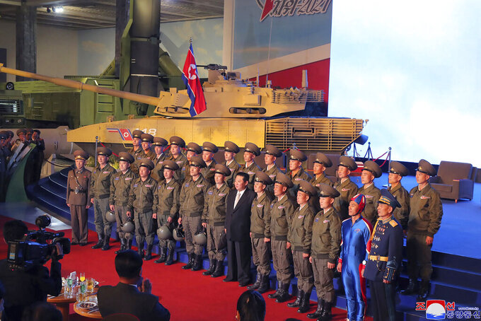 """In this photo provided by the North Korean government, North Korean leader Kim Jong Un, center, poses for a group photo with fighter pilots who made the demonstration flight at the opening of an exhibition of weapons systems in Pyongyang, North Korea, Monday, Oct. 11, 2021. Kim reviewed the rare exhibition and vowed to build an """"invincible"""" military, as he accused the United States of creating regional tensions and lacking action to prove it has no hostile intent toward the North, state media reported Tuesday. Independent journalists were not given access to cover the event depicted in this image distributed by the North Korean government. The content of this image is as provided and cannot be independently verified. Korean language watermark on image as provided by source reads: """"KCNA"""" which is the abbreviation for Korean Central News Agency. (Korean Central News Agency/Korea News Service via AP)"""