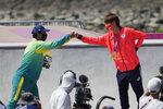 Bronze medalist Kelvin Hoefler of Brazil, left, fist bumps gold medalist Yuto Horigome of Japan after the men's street skateboarding finals at the 2020 Summer Olympics, Sunday, July 25, 2021, in Tokyo, Japan. (AP Photo/Jae C. Hong)