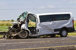 The passenger van involved in a three-vehicle crash Saturday, July 20, 2019, that left five dead and seven injured sits on U.S. 59 in South Texas. Multiple people traveling in the passenger van were pronounced dead at the scene of the crash. Seven people total were injured. (Shelby Miller/The Victoria Advocate via AP)