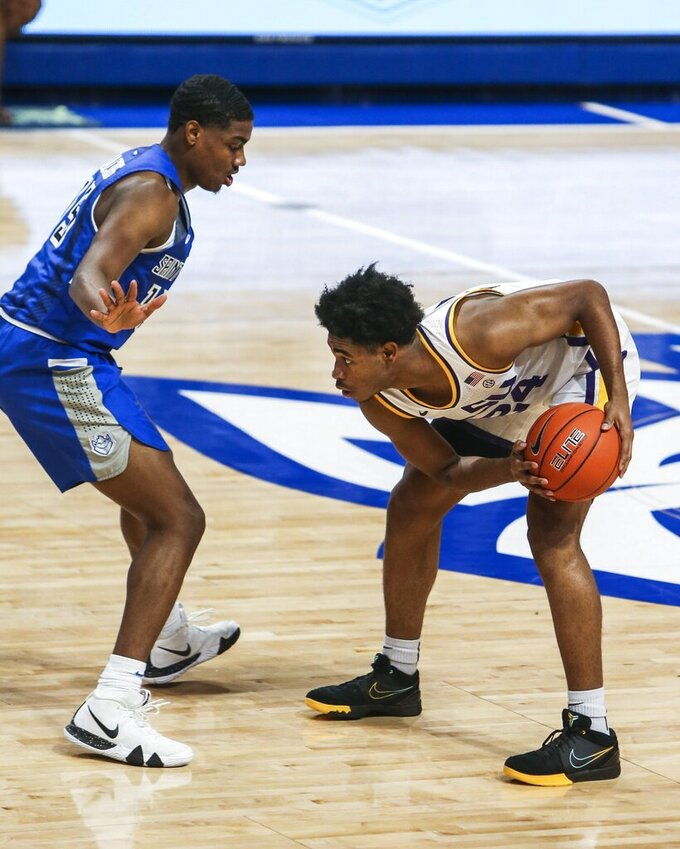 Louisiana State guard Cam Thomas, right, holds onto the ball while looking to pass as Saint Louis guard Demarius Jacobs (15) defends him during the first half of an NCAA college basketball game in St. Louis, Mo., Saturday, Nov. 28, 2020.  (Cheyenne Boone/St. Louis Post-Dispatch via AP)