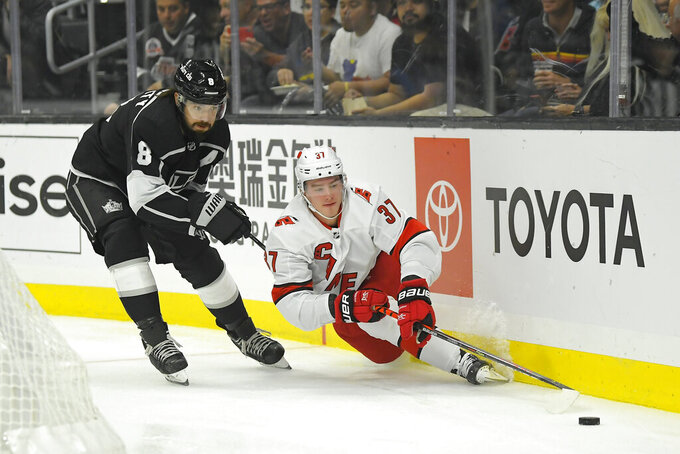 Carolina Hurricanes right wing Andrei Svechnikov, right, falls while under pressure from Los Angeles Kings defenseman Drew Doughty during the first period of an NHL hockey game Tuesday, Oct. 15, 2019, in Los Angeles. (AP Photo/Mark J. Terrill)