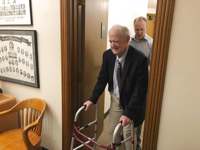 After opening the Oregon state Senate for the 2020 legislature on Monday, Feb. 3, 2020, Senate President Peter Courtney heads to his office from the Senate in Salem, Ore. Courtney appeared despite having been hospitalized with a painful infection and other serious complications in his replacement hip. (AP Photo/Andrew Selsky)