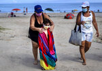 Wearing a mask as a precaution against the spread of the new coronavirus, a woman towels off a child at a beach in Havana, Cuba, Sunday, Oct. 11, 2020. (AP Photo/Ramon Espinosa)