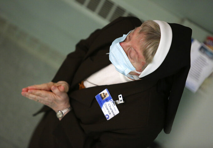 Sister Mary Charlene Ozanick, of the Felician Sisters of North America, prays during morning Mass at St. Anne Home in Greensburg, Pa., on Thursday, March 25, 2021. Communities of Catholic nuns are absorbing devastating losses from outbreaks of the coronavirus. The Felician Sisters lost 21 of their own, in four U.S. convents, a remarkable blow for a community of about 450 women.  (AP Photo/Jessie Wardarski)
