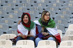 Iranian women wear their country's flag on their shoulders at the Azadi Stadium for the 2022 World Cup qualifier soccer match between Iran and Cambodia, in Tehran, Iran, Thursday, Oct. 10, 2019. Iranian women were freely allowed into the stadium for the first time in decades. The decision follows the death of a young woman who set herself on fire after hearing she could face prison time for sneaking into an Iranian soccer match disguised as a man. (AP Photo/Vahid Salemi)