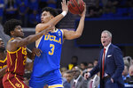 UCLA guard Jules Bernard, center, tries to pass the ball as Southern California guard Ethan Anderson defends while Southern California coach Andy Enfield yells in the background during the first half of an NCAA college basketball game Saturday, Jan. 11, 2020, in Los Angeles. (AP Photo/Mark J. Terrill)