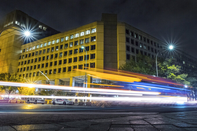 FILE - In this Nov. 1, 2017, file photo, traffic along Pennsylvania Avenue in Washington streaks past the Federal Bureau of Investigation headquarters building. In an alert Wednesday, Oct. 28, 2020, the FBI and other federal agencies warned that cybercriminals are unleashing a wave of data-scrambling extortion attempts against the U.S. healthcare system that could lock up their information systems just as nationwide cases of COVID-19 are spiking. (AP Photo/J. David Ake, File)