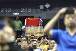 A fan drapes a Chinese national flag over an NBA banner during a preseason NBA basketball game between the Brooklyn Nets and Los Angeles Lakers at the Mercedes Benz Arena in Shanghai, China, Thursday, Oct. 10, 2019. In response to the NBA defending Daryl Morey's freedom of speech, Chinese officials took it away from the Los Angeles Lakers and Brooklyn Nets. All of the usual media sessions surrounding the Lakers-Nets preseason game in Shanghai on Thursday — including a scheduled news conference from NBA Commissioner Adam Silver and postgame news conferences with the teams — were canceled. It was the latest salvo in the rift between the league and China stemming from a since-deleted tweet posted last week by Morey, the general manager of the Houston Rockets. (AP Photo)