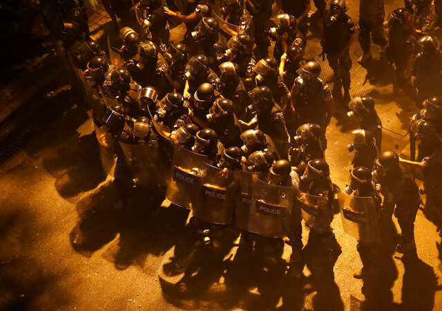 Riot police advance to push back anti-government protesters from a square near the government house, during a protest against the political leadership they blame for the economic and financial crisis, in downtown Beirut, Lebanon, early Friday, June 12, 2020. (AP Photo/Hussein Malla)