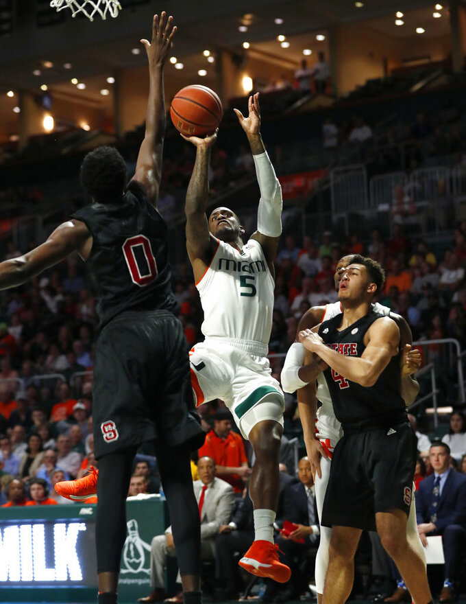 Miami guard Zach Johnson (5) takes a shot against North Carolina State forwards DJ Funderburk (0) and Jericole Hellems (4) during the first half of an NCAA college basketball game, Thursday, Jan. 3, 2019, in Coral Gables, Fla. North Carolina State defeated Miami 87-82. (AP Photo/Wilfredo Lee)