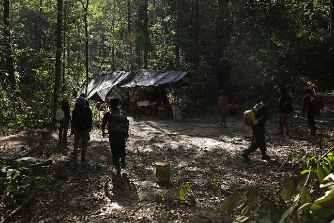 Tenetehara Indigenous men from the Ka'Azar, or Forest Owners, surround a camp of illegal loggers they discovered while patrolling their lands on the Alto Rio Guama reserve in Para state, near the city of Paragominas, Brazil, Tuesday, Sept. 8, 2020. Three Tenetehara Indigenous villages are patrolling to guard against illegal logging, gold mining, ranching, and farming as increasing encroachment and lax government enforcement during COVID-19 have forced the tribe to take matters into their own hands. (AP Photo/Eraldo Peres)