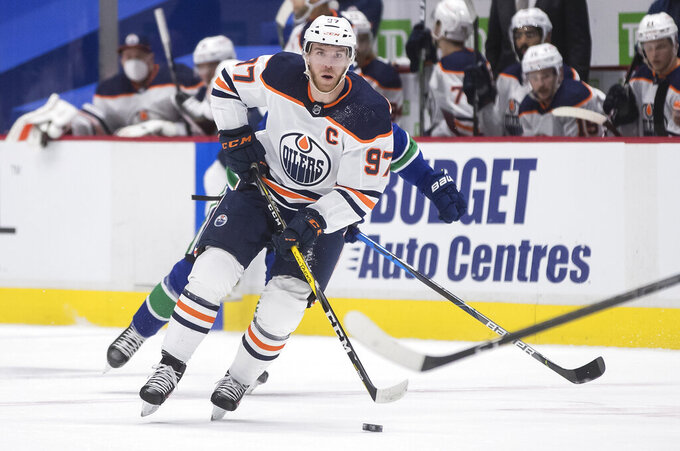 FILE - In this  Tuesday, May 4, 2021 file photo, Edmonton Oilers' Connor McDavid skates with the puck during the first period of an NHL hockey game in Vancouver, British Columbia. The Edmonton captain is in a class by himself with a league-high 104 points in 55 games as the likely Hart Trophy winner as the NHL's MVP. The Oilers will be playing Winnipeg in their first-round series, the team McDavid had the most points against this season with 22 in nine games played. (Darryl Dyck/The Canadian Press via AP, File)