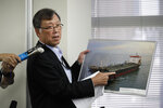 FILE - In this Friday, June 14, 2019 file photo, Yutaka Katada, president of Kokuka Sangyo Co., the Japanese company operating one of two oil tankers attacked near the Strait of Hormuz, shows a photo of the attacked oil tanker during a news conference in Tokyo, Japan. A series of attacks on oil tankers near the Persian Gulf has ratcheted up tensions between the U.S. and Iran -- and raised fears over the safety of one of Asia's most vital energy trade routes, where about a fifth of the world's oil passes through its narrowest at the Strait of Hormuz. (AP Photo/Jae C. Hong, File)