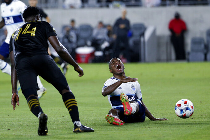 Vancouver Whitecaps midfielder Deiber Caicedo, right, reacts after a foul by Los Angeles FC defender Jesus David Murillo (94) during the second half of an MLS soccer match in Los Angeles, Saturday, July 24, 2021. The game ended in a 2-2 draw. (AP Photo/Ringo H.W. Chiu)