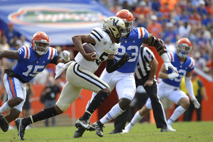 Vanderbilt quarterback Mike Wright (5) scrambles for yardage in front of Florida linebacker Derek Wingo (15) and defensive lineman Princely Umanmielen (33) during the second half of an NCAA college football game, Saturday, Oct. 9, 2021, in Gainesville, Fla. (AP Photo/Phelan M. Ebenhack)