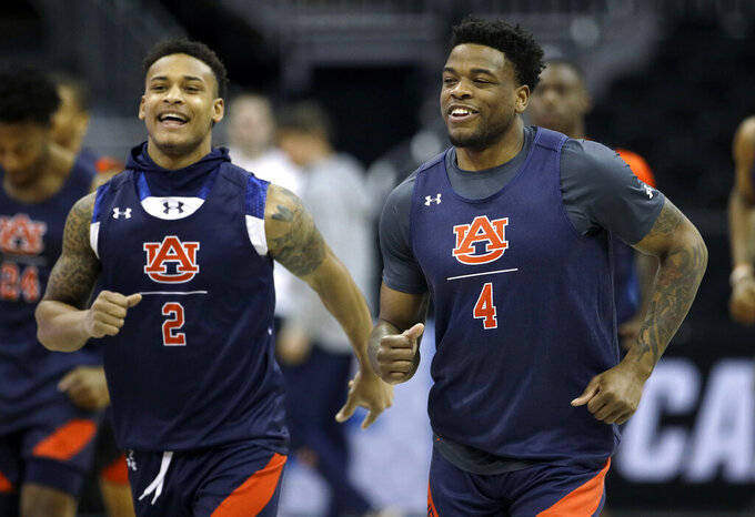 Auburn's Bryce Brown (2) and Malik Dunbar (4) warm up during practice at the NCAA men's college basketball tournament Thursday, March 28, 2019, in Kansas City, Mo. Auburn plays North Carolina in a Midwest Regional semifinal on Friday. (AP Photo/Charlie Riedel)