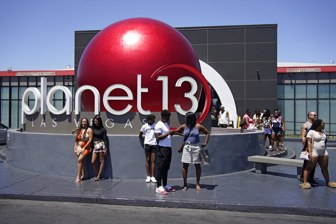 People stand outside of the Planet 13 cannabis dispensary Friday, June 11, 2021, in Las Vegas. A new law approved by the state Legislature and signed by Democratic Gov. Steve Sisolak paves the way for marijuana consumption lounges to open in Nevada next year. At Planet 13 dispensary near the Las Vegas Strip, plans are already being made for a consumption area. (AP Photo/John Locher)