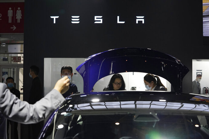 FILE - In this Sunday, Sept. 27, 2020, file photo, attendees wearing masks to protect from the coronavirus look at cars at the Tesla booth during the Auto China 2020 show in Beijing. Tesla Inc. is balking at recalling about 159,000 vehicles with potentially defective touch screens, so U.S. safety regulators are moving to force the company to take action, in news announced Wednesday, Jan. 13, 2021. (AP Photo/Ng Han Guan, File)