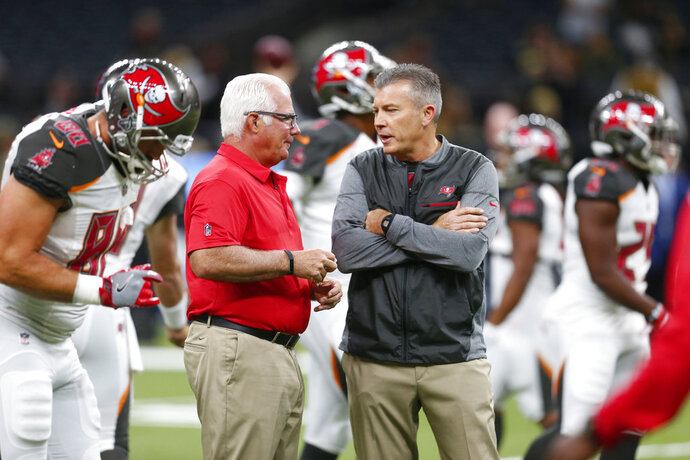 FILE - In this Nov. 5, 2017, file photo, Tampa Bay Buccaneers defensive coordinator Mike Smith, left, talks with head coach Dirk Koetter before an NFL football game against the New Orleans Saints, in New Orleans. The Bucs' defensive woes have put the heat on coordinator Mike Smith, a former head coach of the Falcons. But head coach Dirk Koetter has resisted calls to make a change.