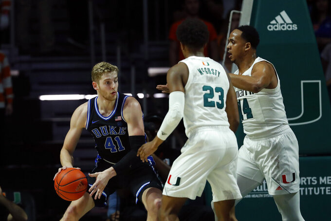 Duke forward Jack White (41) looks for an opening past Miami guard Kameron McGusty (23) and center Rodney Miller Jr. (14) during the first half of an NCAA college basketball game, Saturday, Jan. 4, 2020, in Coral Gables, Fla. (AP Photo/Wilfredo Lee)