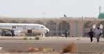 People walk away from the runway following an explosion at the airport in Aden, Yemen, shortly after a plane carrying the newly formed Cabinet landed on Wednesday, Dec. 30, 2020. No one on board the government plane was hurt but initial reports said several people at the airport were killed. (AP Photo/ Wael Qubady)