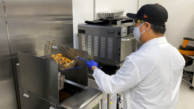 Nathan Foot, R&D chef at Impossible Foods, takes its new meatless nuggets out of a deep fryer in the company's test kitchen on Sept. 21, 2021 in Redwood City, Calif. The plant-based nuggets taste are designed to taste like chicken.  (AP Photo/Terry Chea)