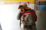 In this Tuesday, Nov. 19, 2019 photo, a woman who arrived in an ambulance with a man injured during clashes between security forces and supporters of former President Evo Morales cries at the Bolivian-Dutch Hospital, in El Alto, on the outskirts of La Paz, Bolivia. At least one person was killed when security forces launched an operation to supply gasoline from a major fuel plant that had been blockaded by Morales' backers. (AP Photo/Natacha Pisarenko)