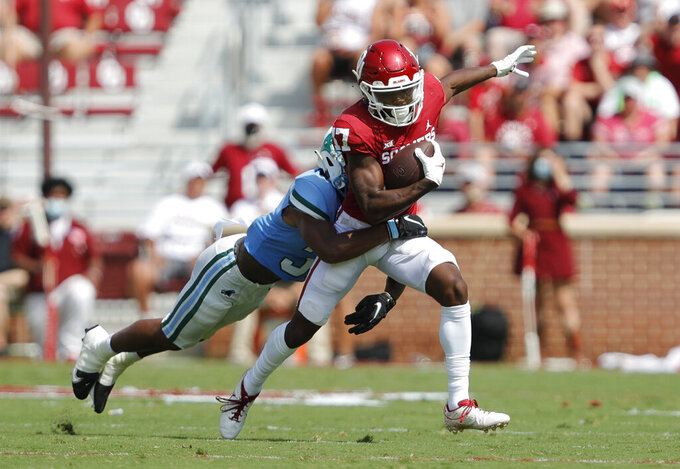 Oklahoma wide receiver Marvin Mims (17) fights off a tackle by Tulane safety Macon Clark (37) during a NCAA college football game Saturday, Sept. 4, 2021, in Norman, Okla. (AP Photo/Alonzo Adams)