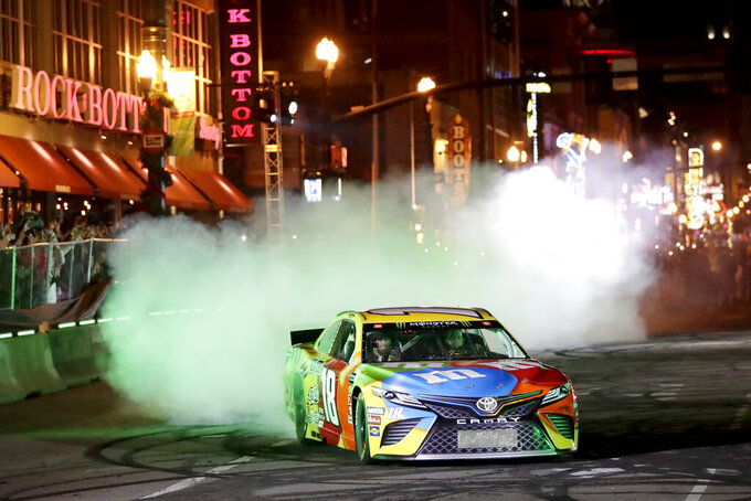 NASCAR driver Kyle Busch does a burnout in the Burnouts on Broadway competition Wednesday, Dec. 4, 2019, during NASCAR Champion's Week in Nashville, Tenn. (AP Photo/Mark Humphrey)