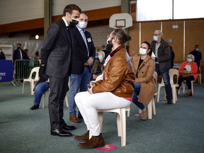 French President Emmanuel Macron talks to a man after he received a Pfizer COVID-19 vaccine at the vaccination center of Valenciennes, northern France, Tuesday, March 23, 2021. The French government has backed off from ordering a tough lockdown for Paris and several other regions despite an increasingly alarming situation at hospitals with a rise in the number of COVID-19 patients. (Yoan Valat/Pool Photo via AP)