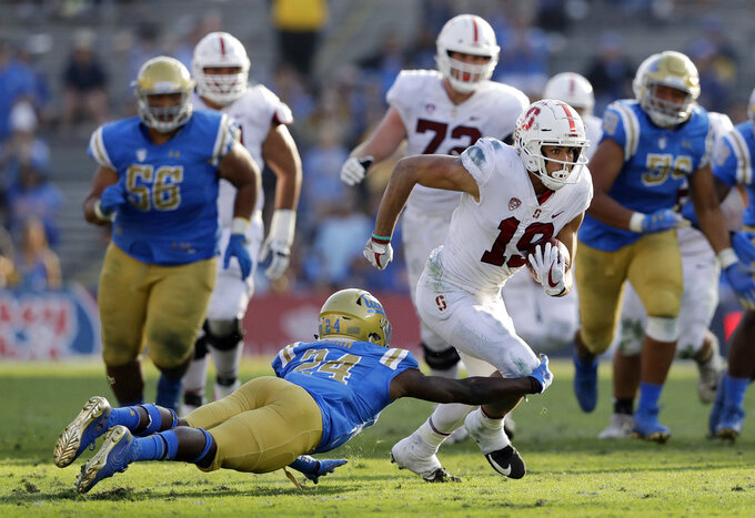 Stanford wide receiver JJ Arcega-Whiteside, right, runs after a reception as UCLA defensive back Jay Shaw, bottom left, attempts a tackle during the second half of an NCAA college football game Saturday, Nov. 24, 2018, in Pasadena, Calif. (AP Photo/Marcio Jose Sanchez)