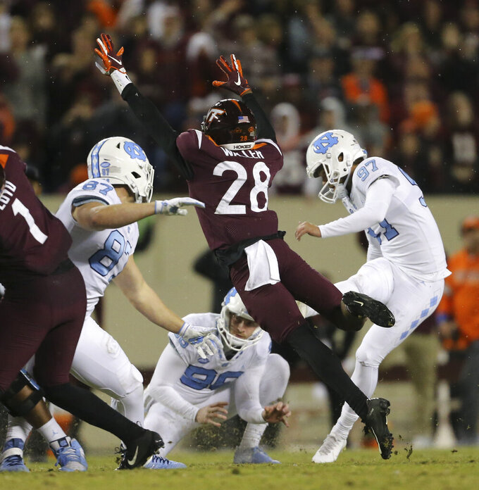 Virginia Tech' Jermaine Waller (28) blocks a field-goal attempt by North Carolina's Noah Ruggles (97) during overtime in an NCAA college football game Saturday, Oct. 19, 2019, in Blacksburg, Va. (Matt Gentry/The Roanoke Times via AP)