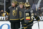 Vegas Golden Knights' Mark Stone, left, and Chandler Stephenson, right, celebrate after Cody Glass, center, scored against the Minnesota Wild during the second period of an NHL hockey game Monday, March 1, 2021, in Las Vegas. (AP Photo/John Locher)