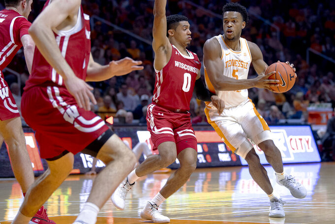 Tennessee guard Josiah-Jordan James (5) dribbles the ball as Wisconsin guard D'Mitrik Trice (0) defends during an NCAA college basketball game, Saturday, Dec. 28, 2019 in Knoxville, Tenn. on Saturday, Dec. 28, 2019. (Calvin Mattheis/Knoxville News Sentinel via AP)