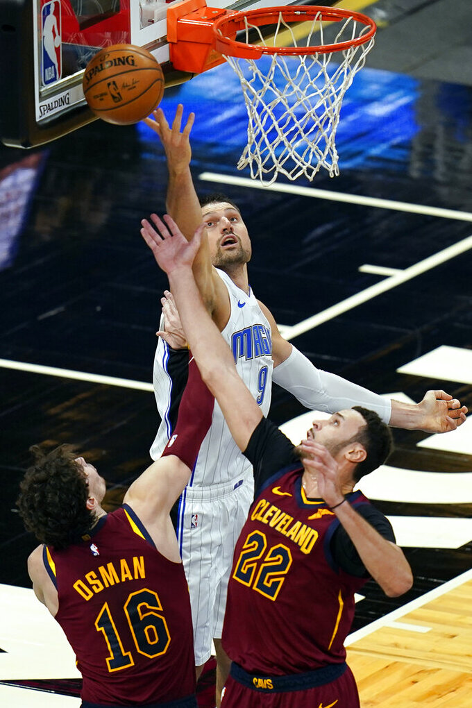 Orlando Magic center Nikola Vucevic, center, goes up for a rebound against Cleveland Cavaliers forward Cedi Osman (16) and forward Larry Nance Jr. (22) during the first half of an NBA basketball game, Monday, Jan. 4, 2021, in Orlando, Fla. (AP Photo/John Raoux)