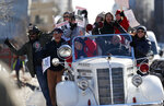 Denver teachers ride on the back of a vintage Denver Fire Department truck past a strike rally on the west steps of the State Capitol Monday, Feb. 11, 2019, in Denver. The strike is the first for teachers in Denver since 1994 and centers on base pay. (AP Photo/David Zalubowski)