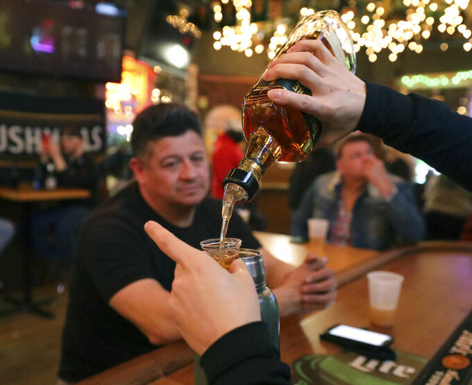 A waiter of Lottie's Pub pours alcohol into a shot glass as Frank Robelli, left, and Cliff Naumann watch Saturday, March 13, 2021, in Chicago's Bucktown neighborhood. The NCAA Tournament and bars were made for each other. This year, the tournament's back, and bars and restaurants, some shuttered for months, are open for March Madness, though things may look a little different. (AP Photo/Shafkat Anowar)