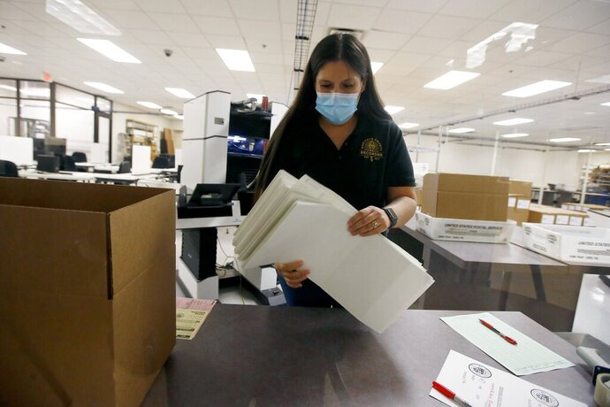 Ballots are handled after the votes were counted at the Maricopa County Recorder's Office for the primary election Tuesday, Aug. 4, 2020, in Phoenix. (AP Photo/Ross D. Franklin)
