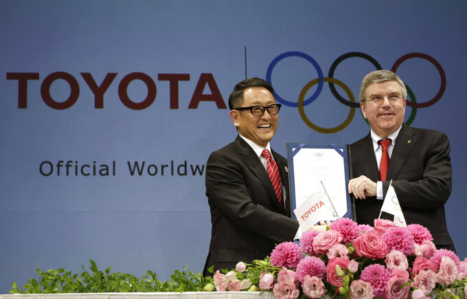 FILE - In this March 13, 2015 file photo, Toyota President and CEO Akio Toyoda, left, and IOC President Thomas Bach pose with a signed document during a press conference in Tokyo as Toyota signed on as a worldwide Olympic sponsor in a landmark deal, becoming the first car company to join the IOC's top-tier marketing program. Toyota won't be airing any Olympic-themed advertisements on Japanese TV during the Tokyo Games despite being one of the IOC's top corporate sponsors. The unusual decision by the country's top automaker underlines how polarizing the Games have become in Japan as COVID-19 infections rise ahead of the July 23, 2021, opening ceremony.(AP Photo/Eugene Hoshiko, File)