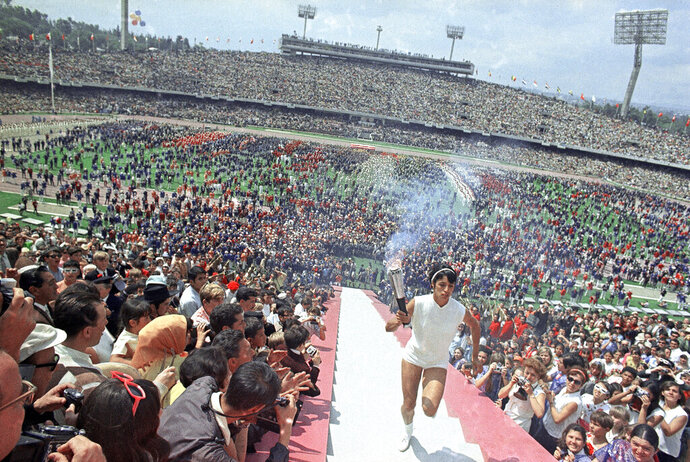 FIK]LE - In this Oct. 12, 1968, file photo, Mexican hurdler Enriqueta Basilio, the first woman to make the final run of the torch and to light the Olympic flame, carries the Olympic torch up the 90 steps to the Olympic flame cauldron in the Olympic Stadium during opening ceremonies for the Olympic Games in Mexico City. (AP Photo/File)