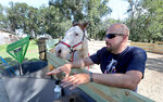 This photo taken Sept. 25, 2019, shows Chris Reder, of DTOM/22 Ranch,in Warner, S.D., right, talking about how he uses Max, a therapy horse, left, to work with Veterans. (John Davis/Aberdeen American News via AP) **NOT AN AP PHOTO MEMBER**