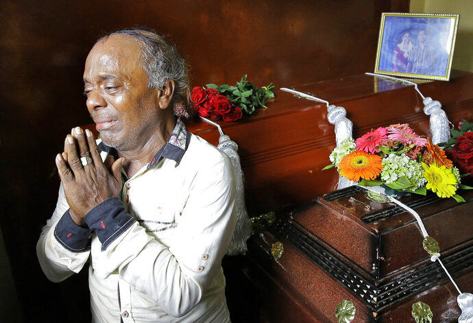 Baby Joseph Gomes prays standing next to coffins of his family members killed in the Easter Sunday bombings in Colombo, Sri Lanka, Tuesday, April 23, 2019. Gomes lost five members of his family. The six near-simultaneous attacks on three churches and three luxury hotels and three related blasts later Sunday were the South Asian island nation's deadliest violence in a decade while Sri Lanka police arrested 40 suspects in the wake of a state of emergency that took effect Tuesday giving the military war-time powers. (AP Photo/Eranga Jayawardena)