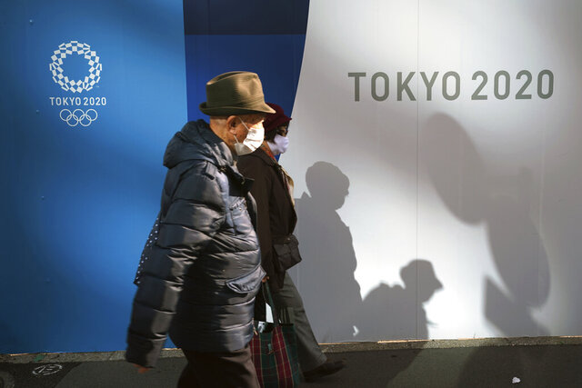 A man and a woman wearing protective masks to help curb the spread of the coronavirus walk in front of logos of Tokyo 2020 Olympics Monday, Nov. 30, 2020, in Tokyo. (AP Photo/Eugene Hoshiko)