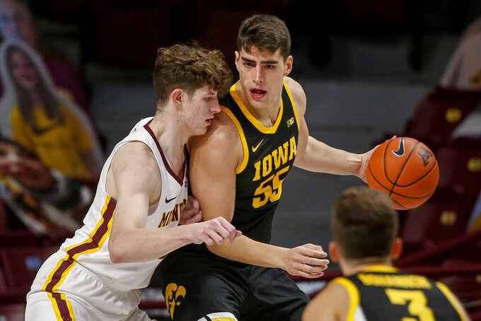 Minnesota center Liam Robbins defends against Iowa center Luka Garza (55) during the first half of an NCAA college basketball game Friday, Dec. 25, 2020, in Minneapolis. (AP Photo/Bruce Kluckhohn)