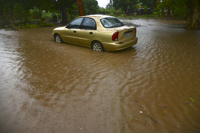 A car sits in flood waters caused by Tropical Storm Laura in Salinas, Puerto Rico, Saturday, Aug. 22, 2020. Laura began flinging rain across Puerto Rico and the Virgin Islands on Saturday morning and was expected to drench the Dominican Republic, Haiti and parts of Cuba during the day on its westward course. (AP Photo/Carlos Giusti)