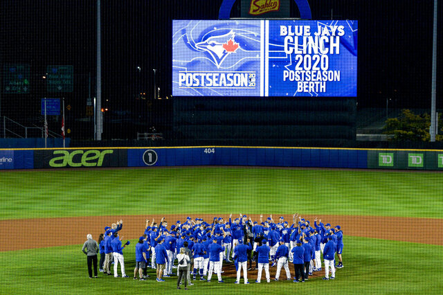 Toronto Blue Jays players, coaches and staff celebrate a 4-1 win over the New York Yankees in a baseball game in Buffalo, N.Y., Thursday, Sept. 24, 2020. Toronto clinched a postseason berth with the win. (AP Photo/Adrian Kraus)