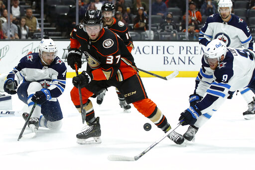 Anaheim Ducks center Mason McTavish (37) and Winnipeg Jets center Andrew Copp (9) work for the puck with defenseman Neal Pionk (4) watching during the second period of an NHL hockey game in Anaheim, Calif., Wednesday, Oct. 13, 2021. (AP Photo/Alex Gallardo)