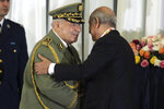 FILE - In this photo taken Thursday, Dec. 19, 2019, Algerian military chief Gaid Salah, left, embraces president Abdelmajid Tebboune during an inauguration ceremony in the presidential palace, in Algiers, Algeria, Algerian state media says the country's powerful military chief Gen. Ahmed Gaid Salah has died. (AP Photo/Fateh Guidoum)
