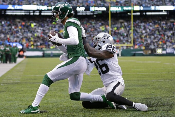 Oakland Raiders cornerback Nevin Lawson (26) attempts to tackles New York Jets' Robby Anderson (11) after Anderson scored during the second half of an NFL football game Sunday, Nov. 24, 2019, in East Rutherford, N.J. (AP Photo/Adam Hunger)